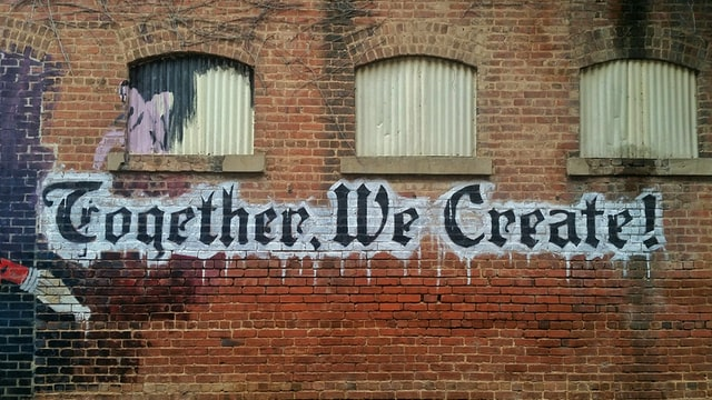 """Street art 'Together we create' on a brick wall  Photo by """"My Life Through A Lens"""" on Unsplash"""